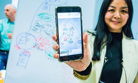 Frau mit Handy vor Flipchart - Wiener Bildungsakademie
